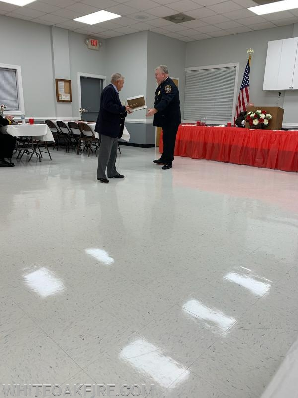 Fire Chief (outgoing President) Martin presenting Life Member Jerry Burton with the President's Appreciation Award for dedicated service to the organization.